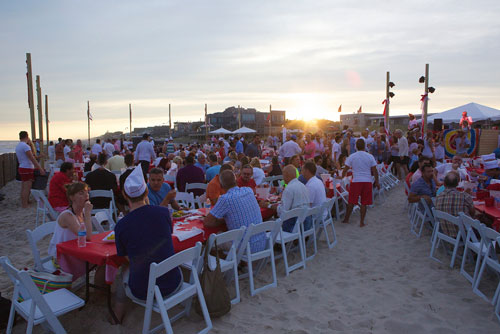 fire island 2015 clambake with white padded folding chairs on the beach with guests eating